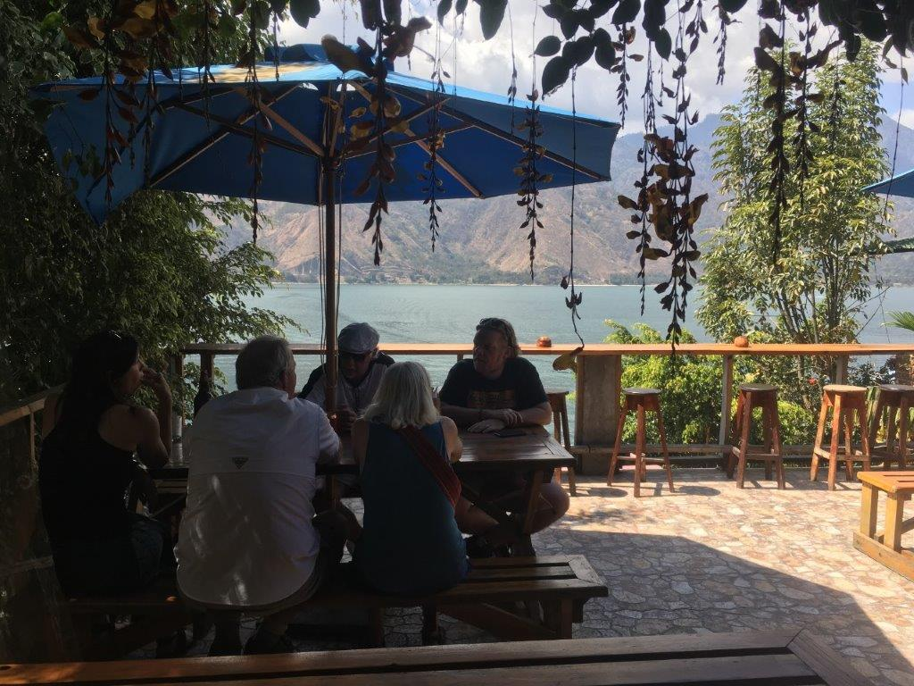 People sitting at a table under an umbrella with a view of the lake in San Pedro La Laguna Lake Atitlan