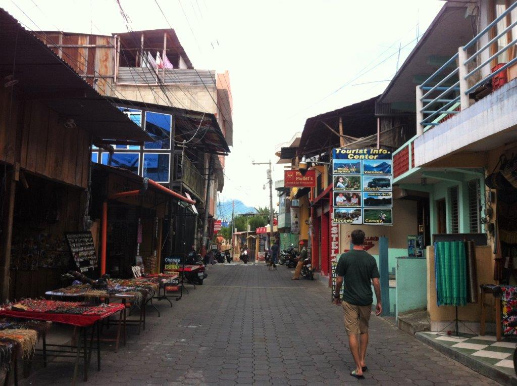 Man walking down street with tables selling handicraft on the main street in San Pedro La Laguna