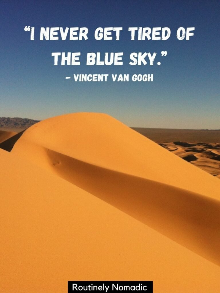 A tall sand dune with small dunes in the background with a blue sky quotes by Vincent Van Gogh that says I never get tired of the blue sky