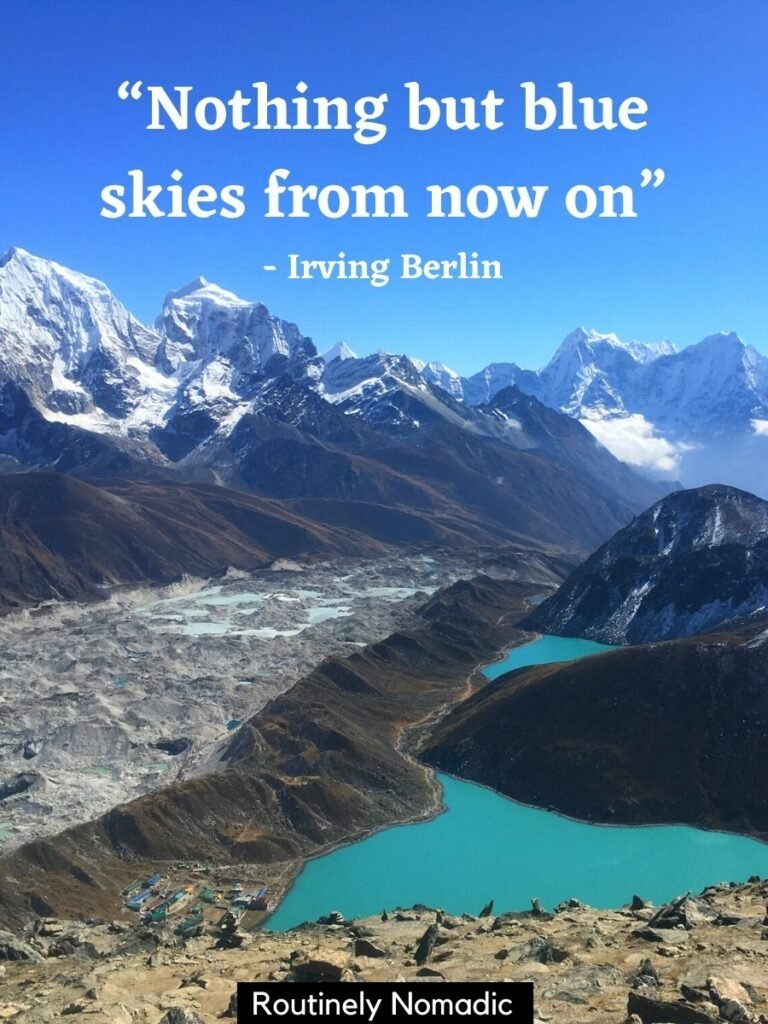 Snow covered mountains with a blue lake below and a blue sky quotes that says nothing but blue skies from now on