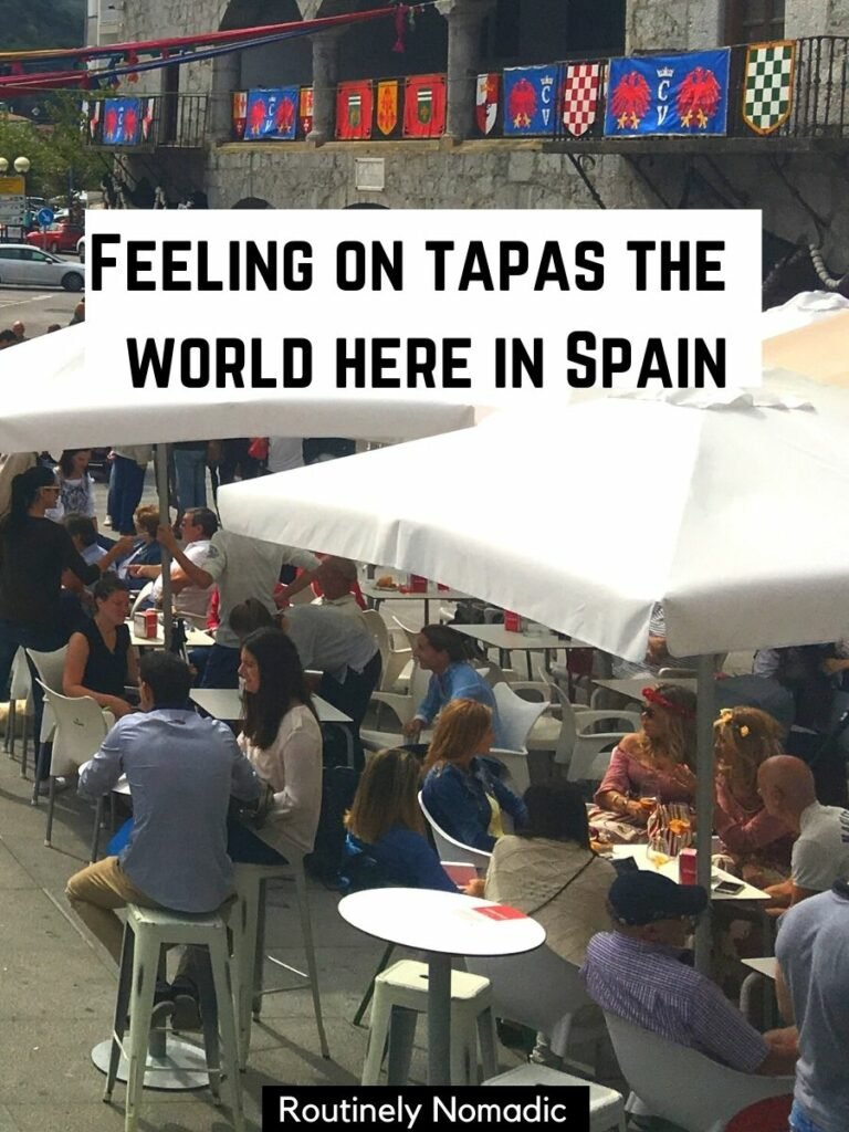 People sitting under umbrellas with a Instagram captions for Spain the reads feeling on tapas the world here in Spain