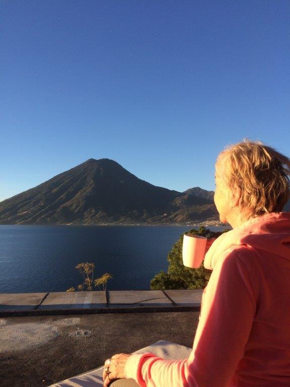 Woman enjoying coffee with view of volcano and lake at Pasajcap Rental the answer to where to stay on Lake Atitlan
