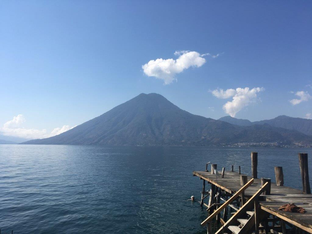 Person swimming in lake in front of volcano at the swimming dock at Pasajcap Rental the answer to where to stay on Lake Atitlan