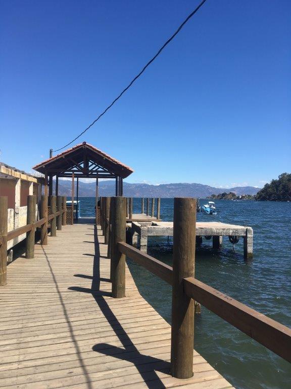 Public dock at San Juan La Laguna Lake Atitlan with a boat coming in