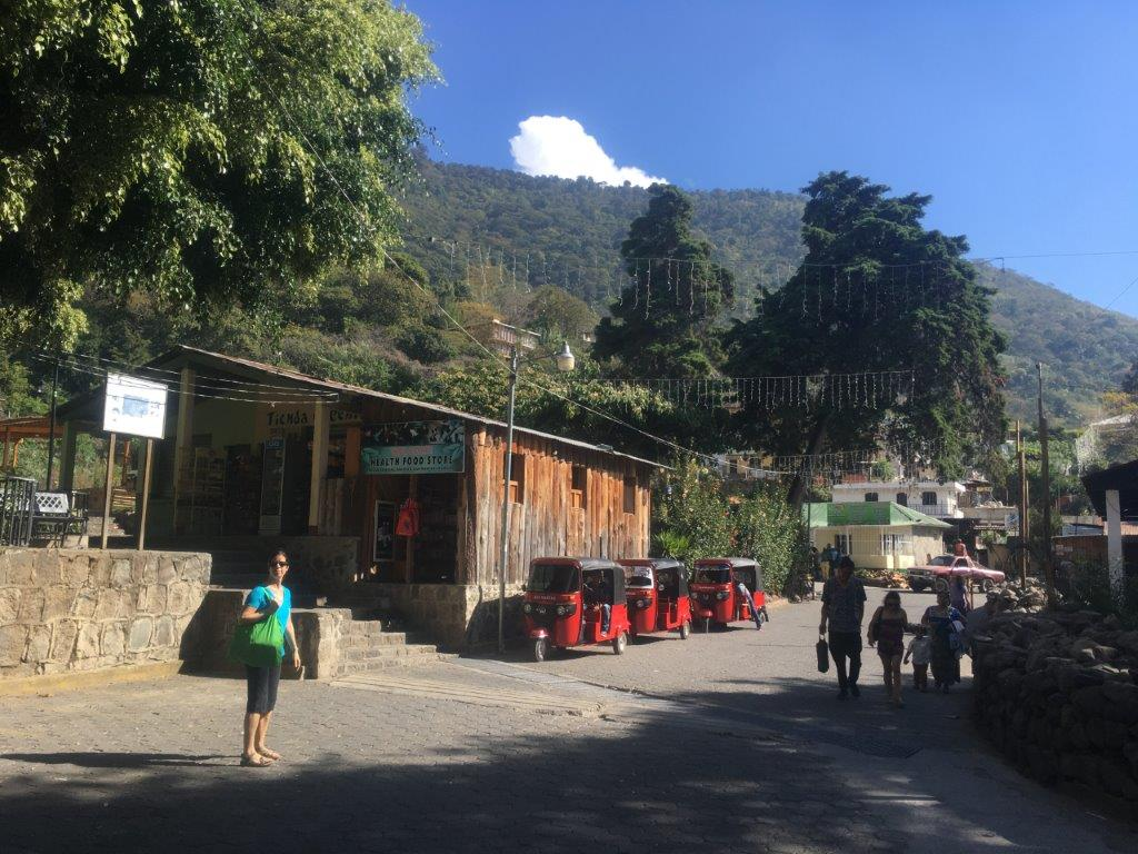 Woman standing with shoppig on San Marcos La Laguna main street near tiendas and tuk tuks