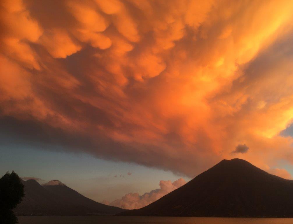 Orange clouds over volcanoes at sunset near San Marcos Lake Atitlan