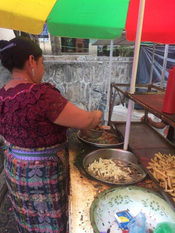 Local woman selling fried chicken and fries at a stall in San Marcos La Laguna Lake Atitlan