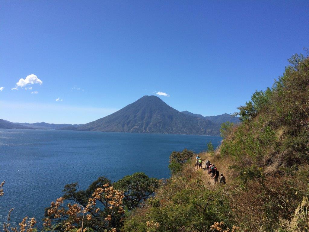 Hikers on trail from Santa Cruz to San Marcos La Laguna Guatemala with Lake Atitlan and volcan San Pedro behind