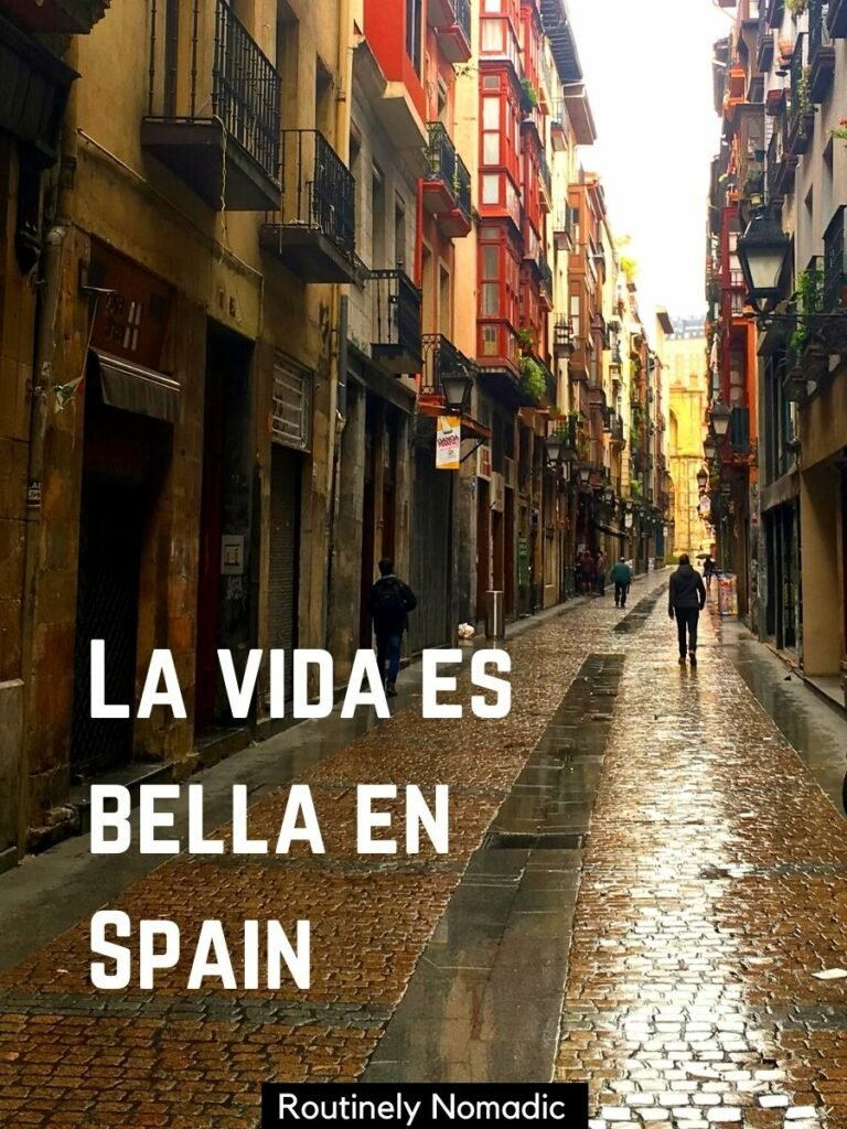 Narrow street with colourful buildings and a spanish captions for pictures that reads la vida es bella en Spain