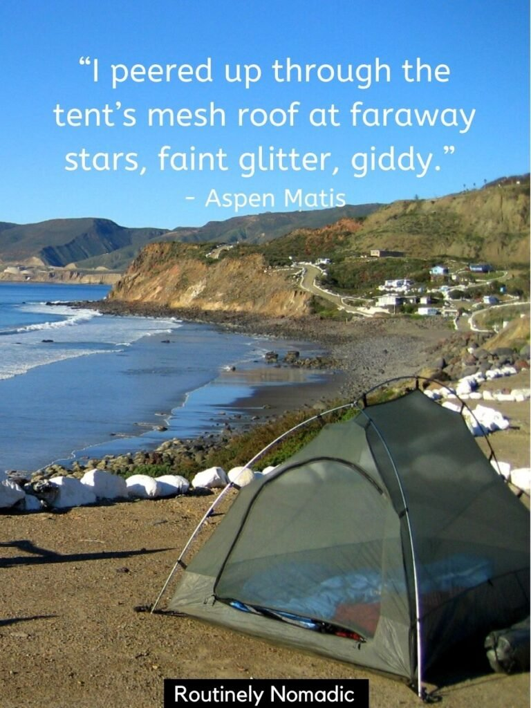 Tent on site above a beach and ocean with a camping quotes ontop by Aspen Matis