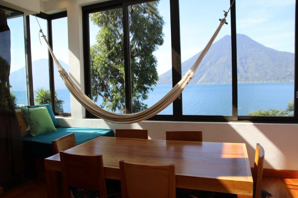 Dining area and reading nook with hammock and view of volcano in a one bedroom unit at Pasajcap Rental the answer to where to stay on Lake Atitlan