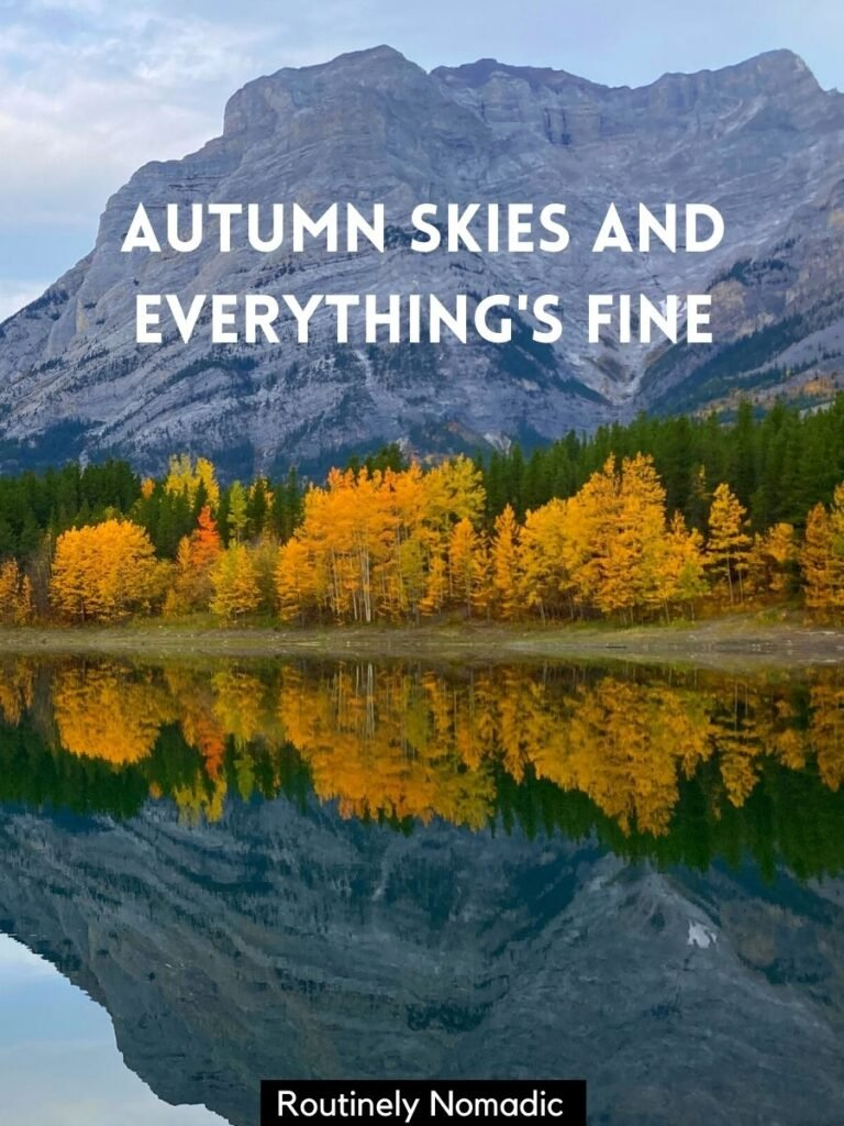 Mountain and yellow trees reflected in a lake with autumn captions for Instagram that reads autumn skies and everything's fine