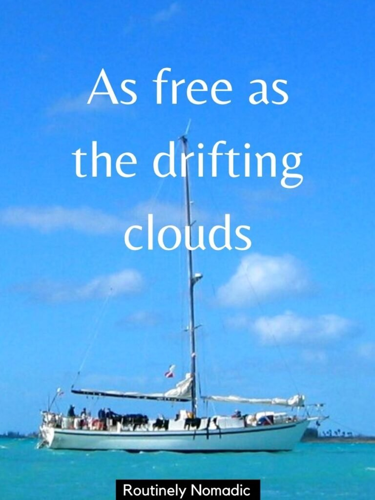 A sailboat on the ocean with a cute captions for vacations that says as free as the drifting clouds