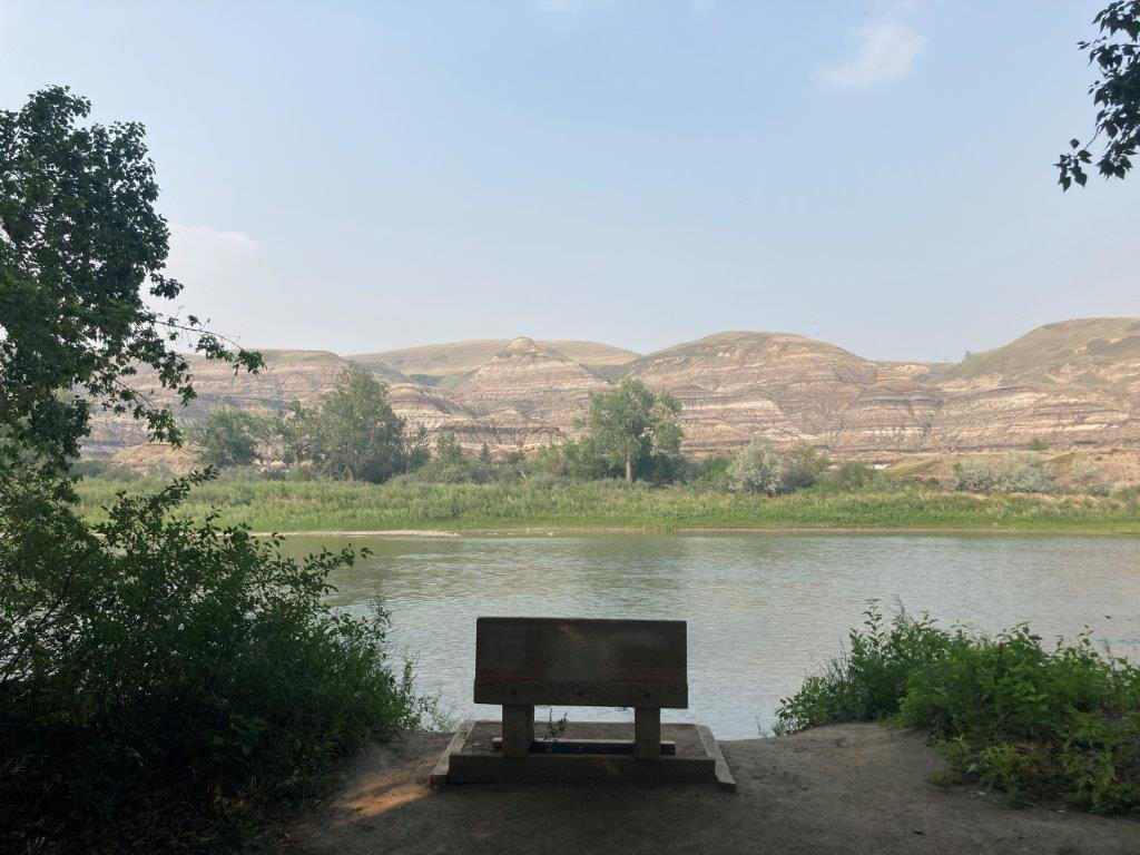 Bench in front of the river on a Drumheller hiking trail