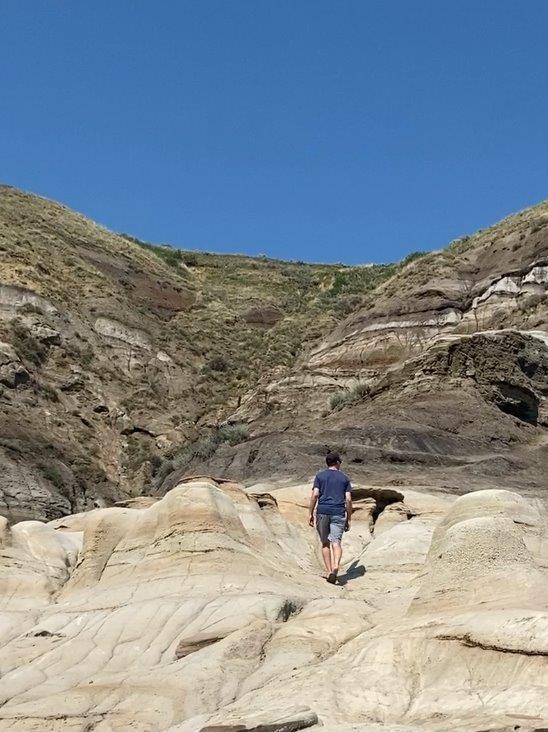 Man walking up towards hill above Drumheller hoodoos