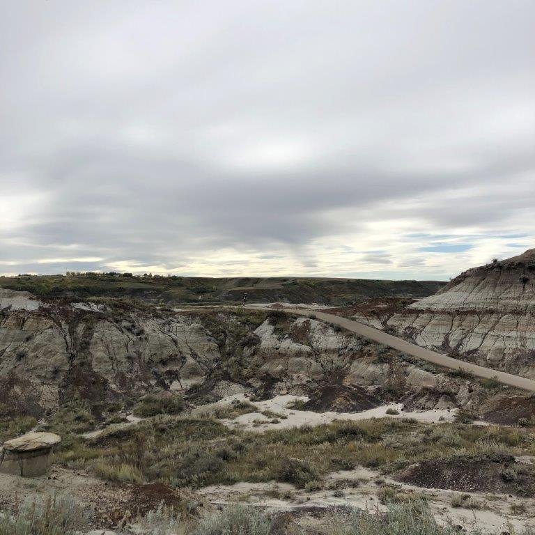 Person hiking on path behind Royal Tyrrell Museum one of Drumheller hikes
