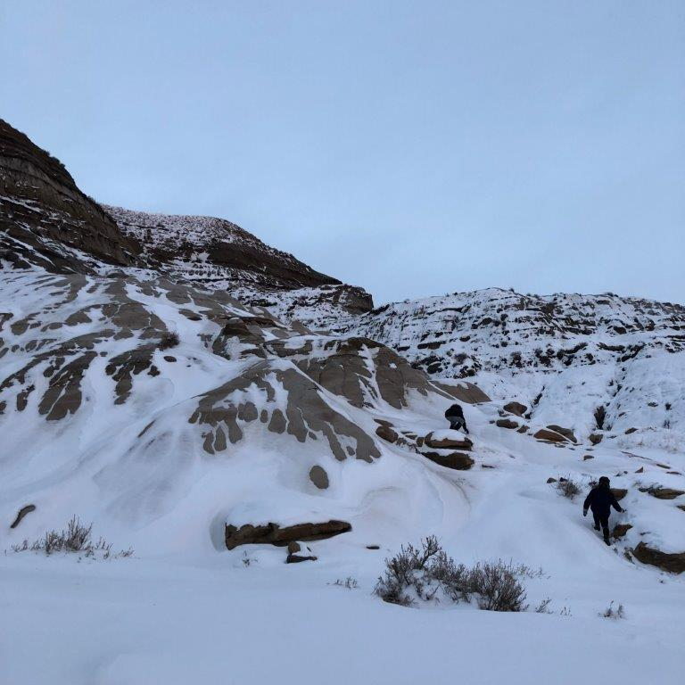People hiking in snow on Badlands one of the things to do in Drumheller in winter