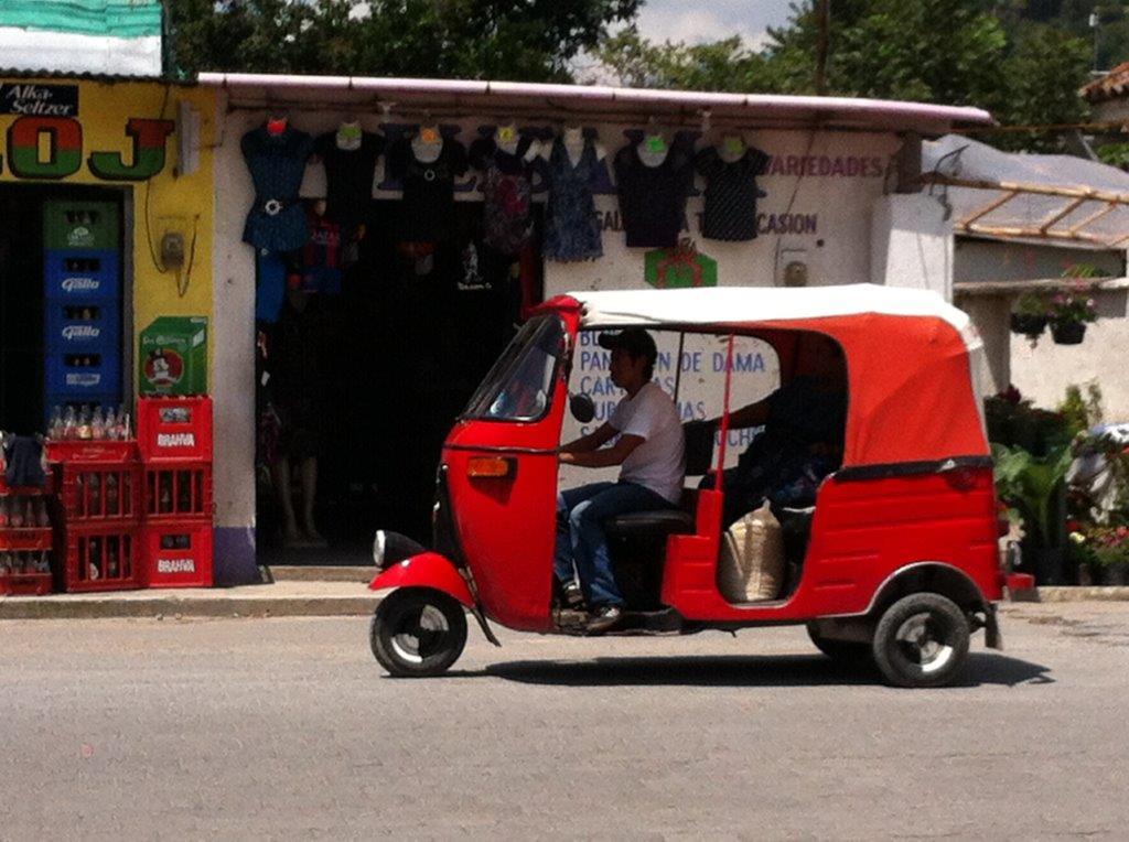 Red tuk tuk driving by at Panajachel Guatemala