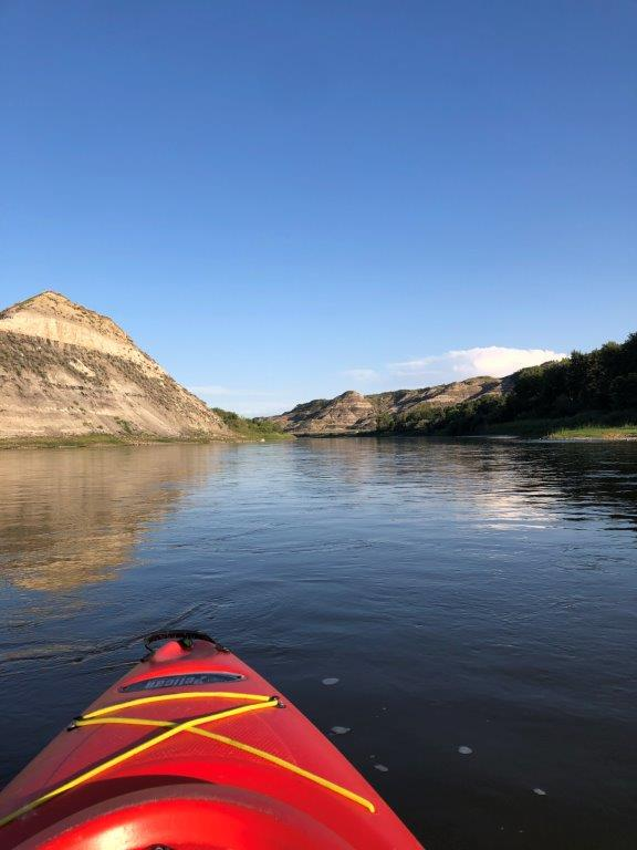 Red kayak on river with badlands hills in distance in Drumheller Alberta