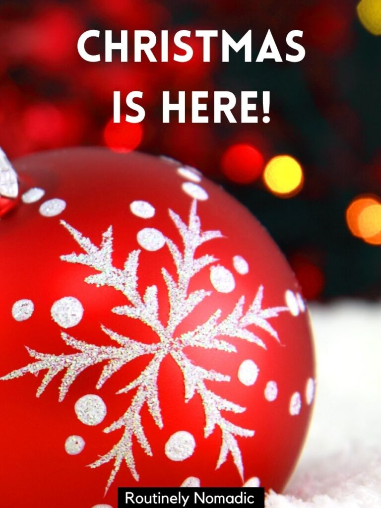 Red tree decoration with short captions for Christmas that says Christmas is here