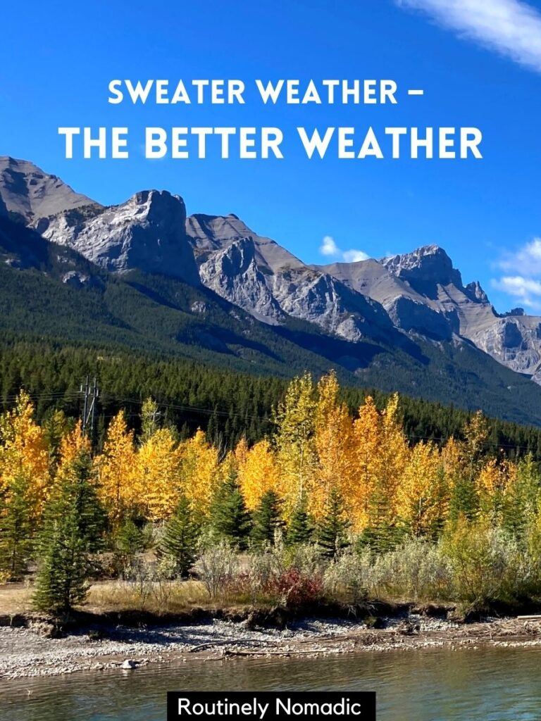 Yellow trees in the fall with mountains in the background and a sweater weather captions that reads sweater weather - the better weather