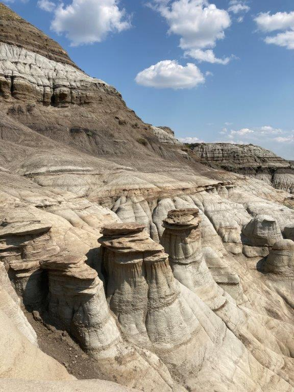 Some of the Drumheller hoodoos with a sandy hill behind