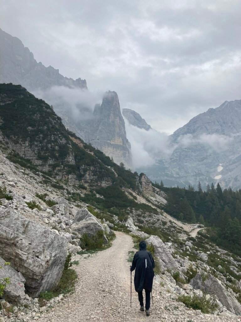 Person hiking in rain gear on the Alta Via 1