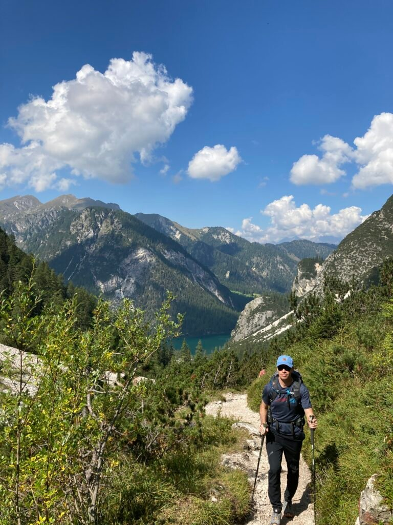 Man hiking on Alta Via 1 with Lago Braies below and mountains behind