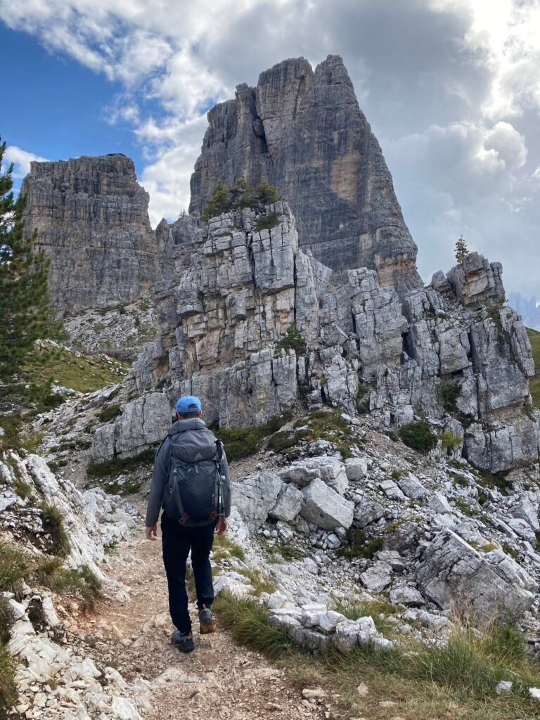 Hiking on the Alta Via 1 Dolomites toward tall rock outcroppings