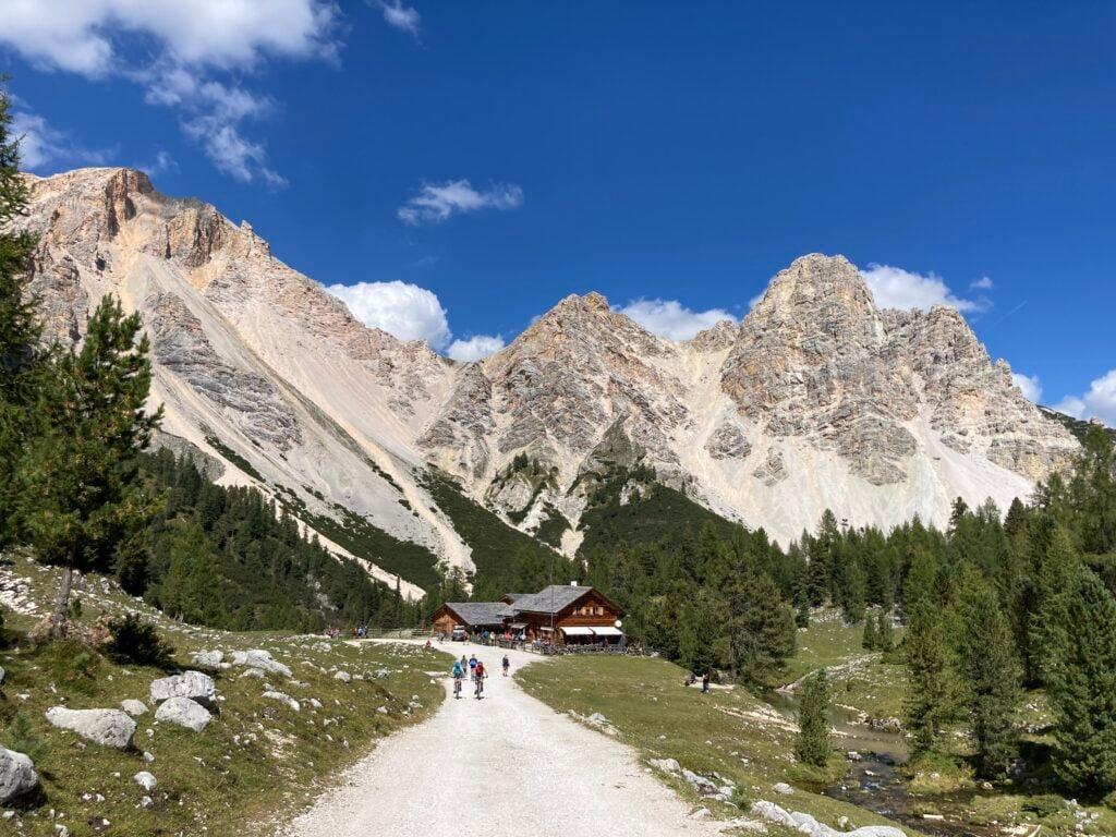 Bikers on road to Rifugio Lavarella, a Alta Via 1 rifugio with mountains behind