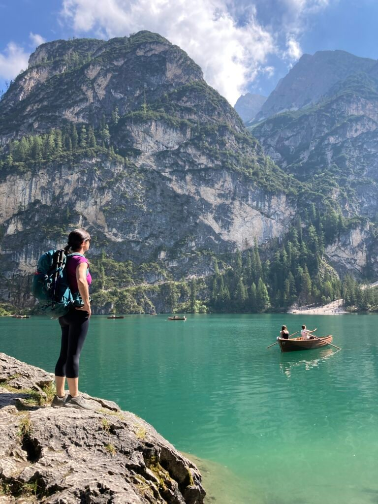 Hiker looking at rowboat on the Lago Braies at the start of the Alta Via 1 Dolomites