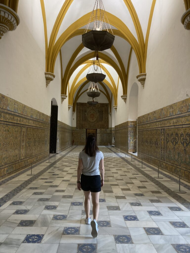 Woman walking down hall in Real Alcazar one of the what to see in Seville Spain