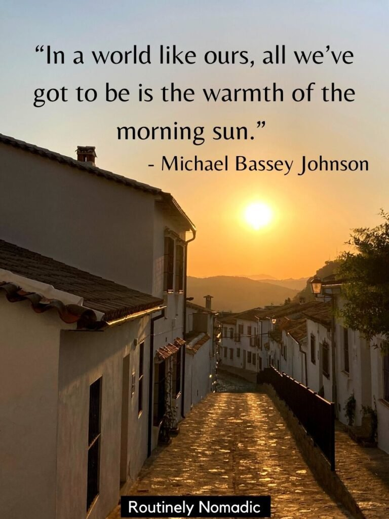 Sun coming up over a street lined with white buildings with a good morning sunshine quotes