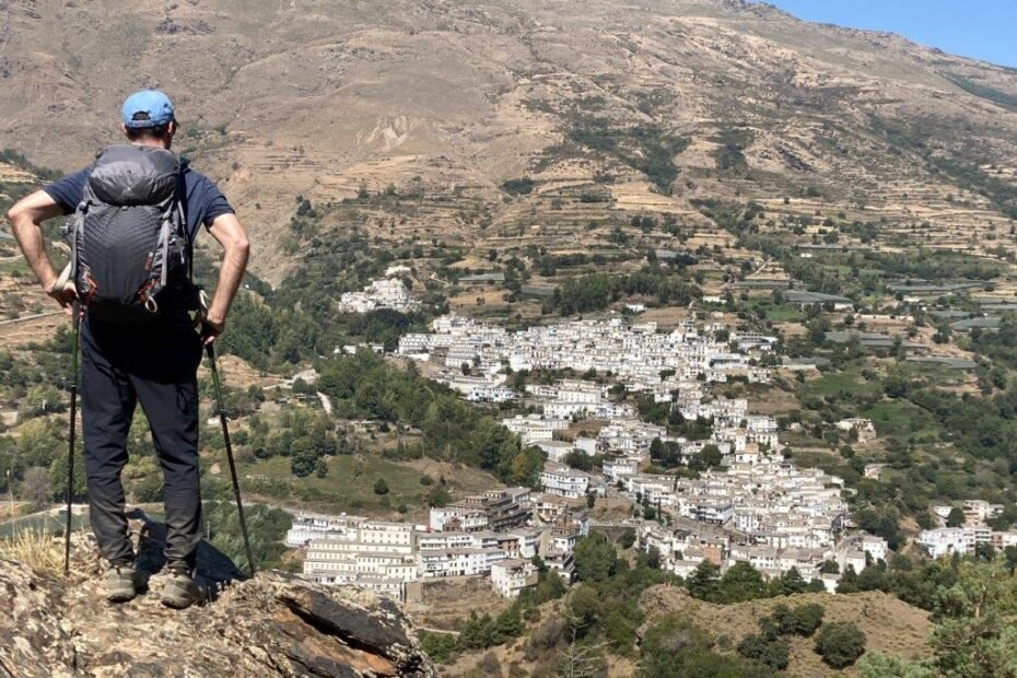 Hiker looking over a white village in Sierra Nevada spain